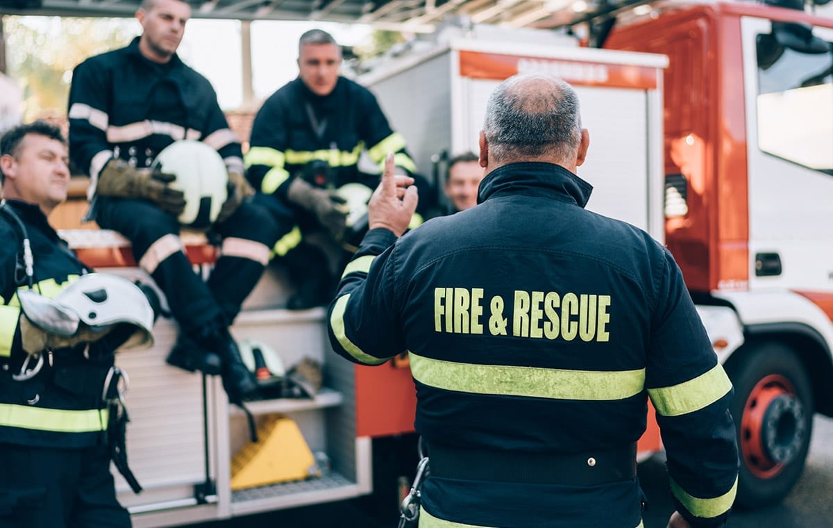 Image of a group of fireman sitting by their firetruck and having a discussion.